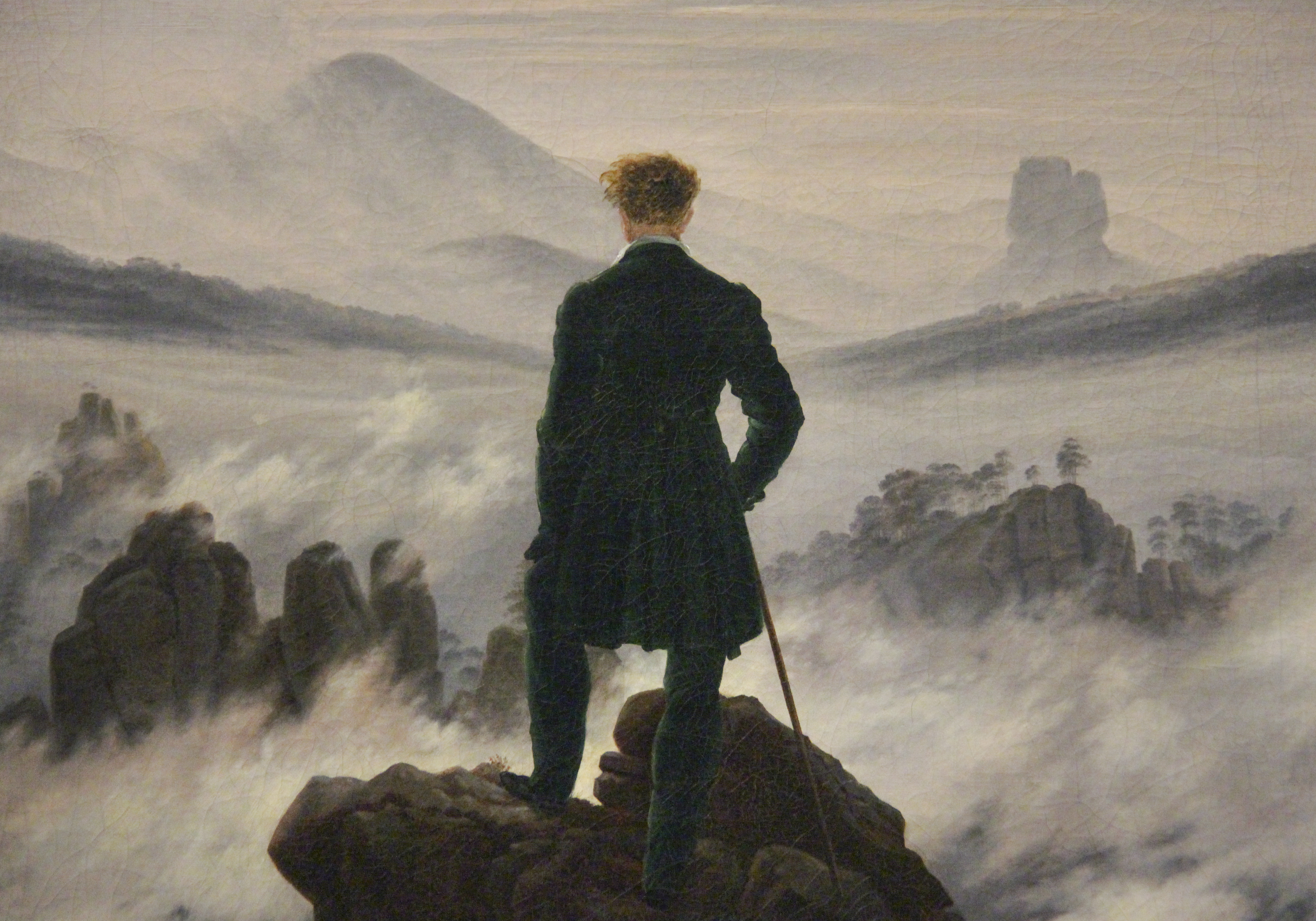 man in dark suit stands on mountain overlooking a sea of clouds