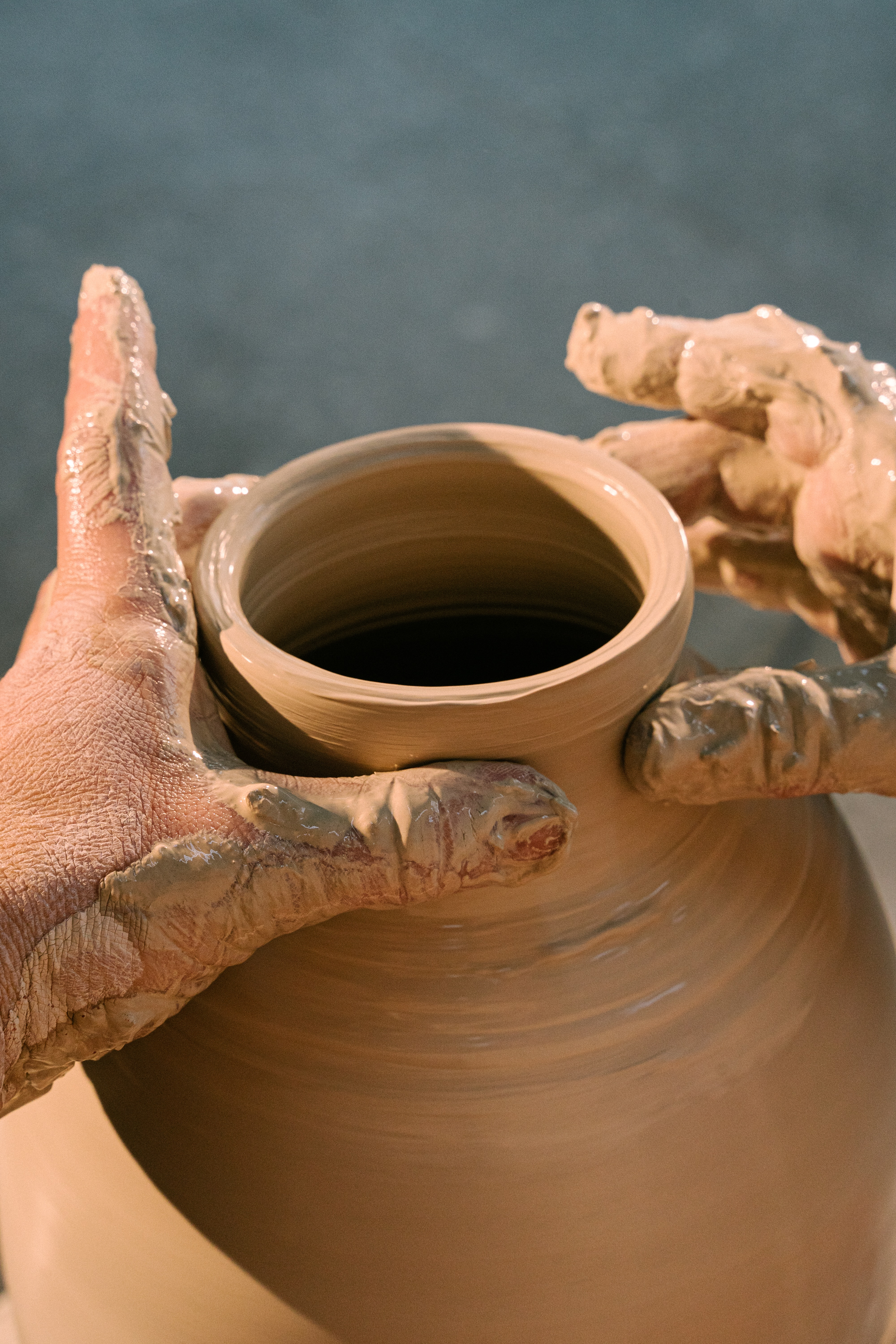 Hands shape the top of an unfinished clay vase