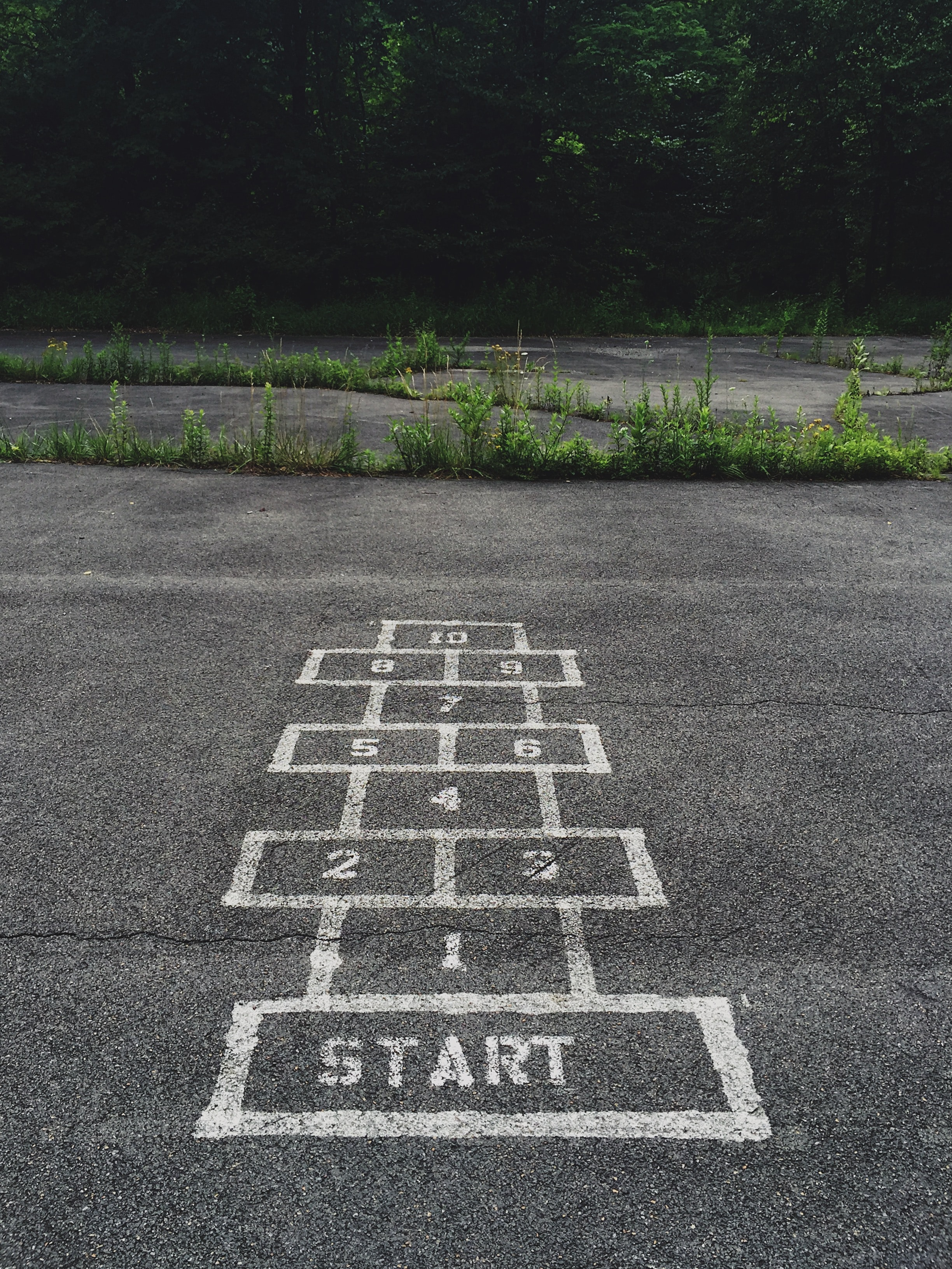 """A hopscotch grid painted on asphalt with the word """"Start"""" painted into the first block."""